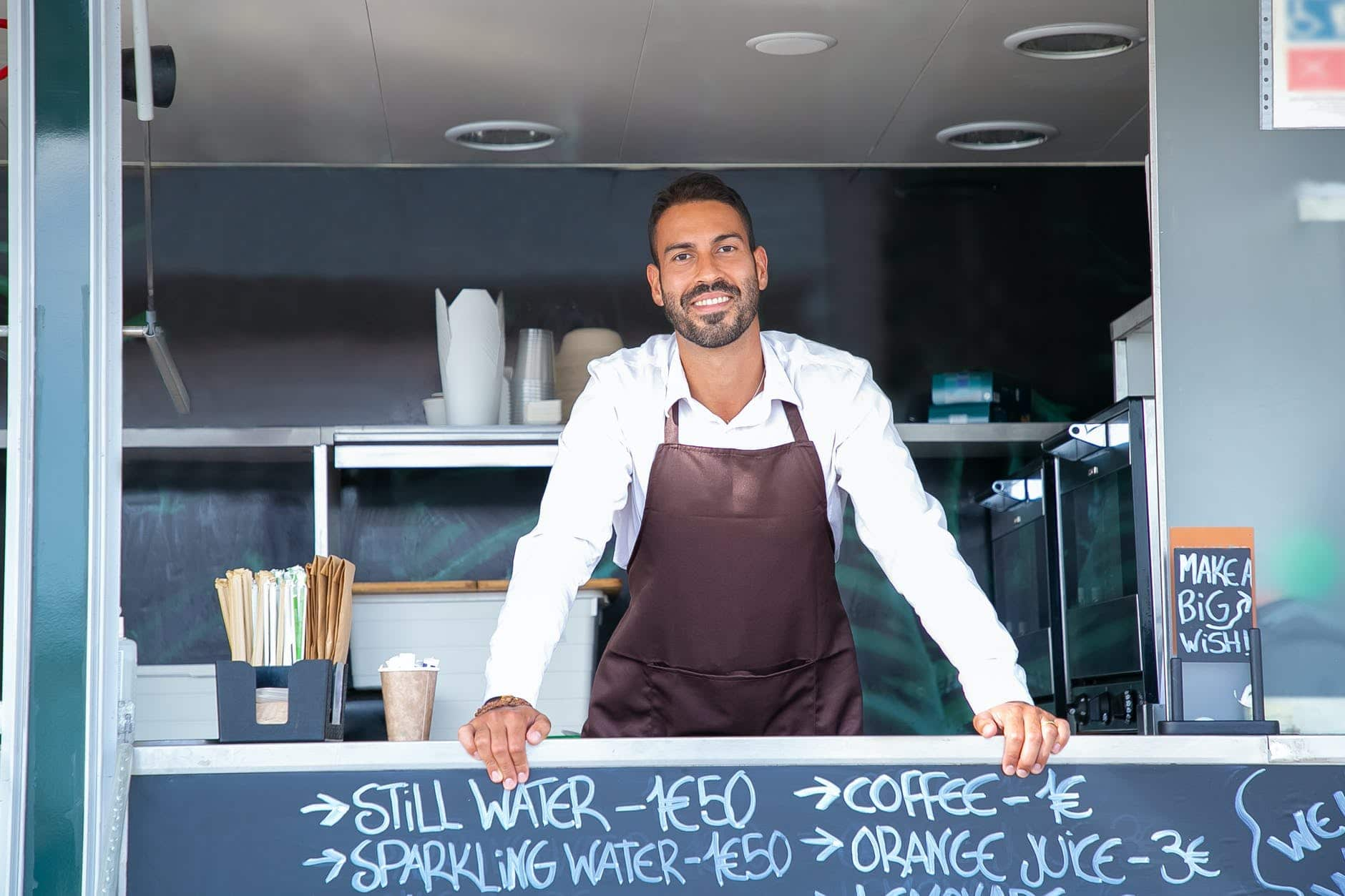 cheerful handsome waiter standing at food track counter