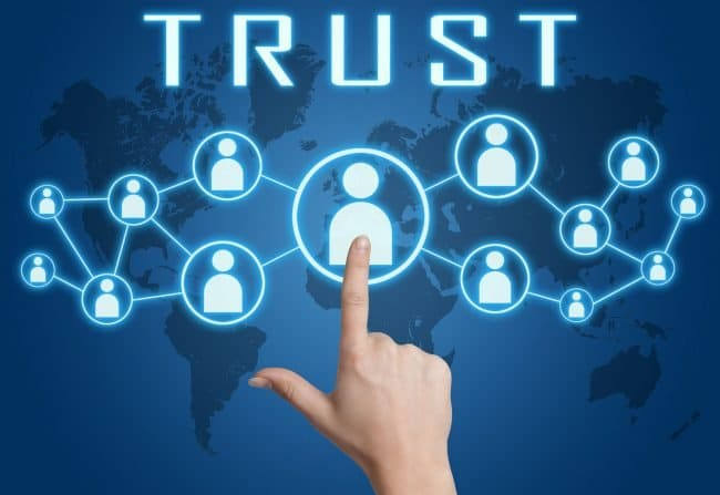 Trust concept with hand pressing social icons on blue world map background.